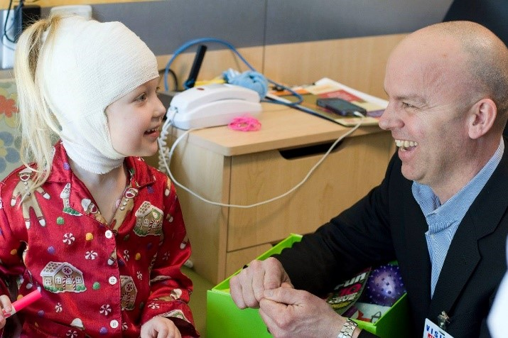 Gary Parisher, President of Cheeriodicals, laughs with one tiny patient while she opens her box of joy.