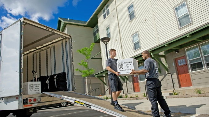 Movers carrying box up truck ramp in front of apartment
