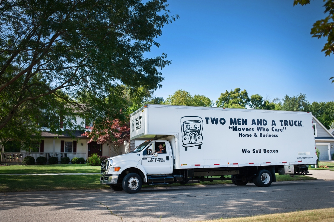 TWO MEN AND A TRUCK truck in front of home