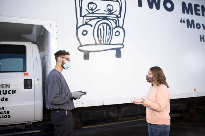 Customer talking with mover next to truck with mask on